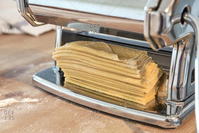 Dough in pasta maker on kitchen island