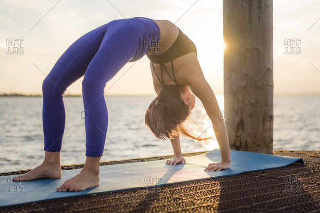 Woman practicing yoga sea against cloudy sky during sunset