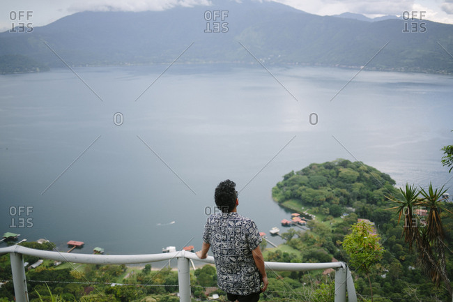 Rear view of man looking at lake while standing on observation point