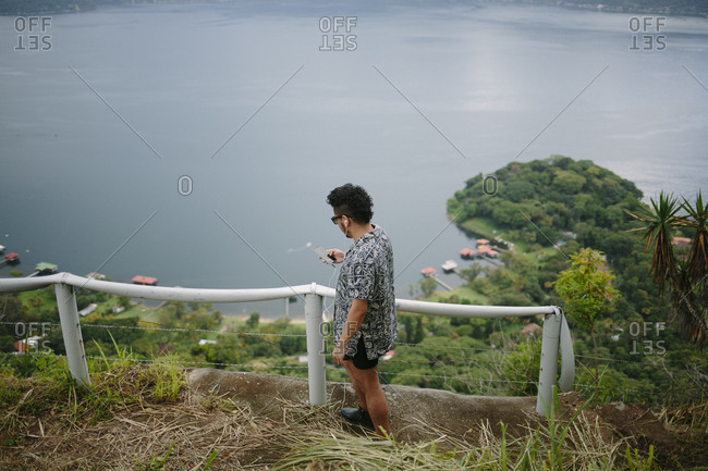 Side view of man using mobile phone while standing at observation point