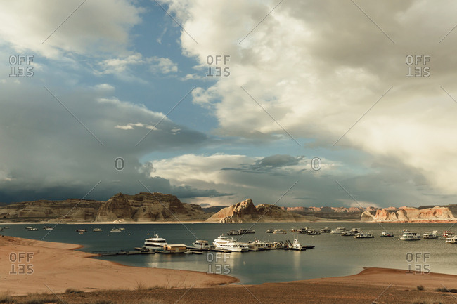 Scenic view of boats in Lake Powell by mountains against cloudy sky