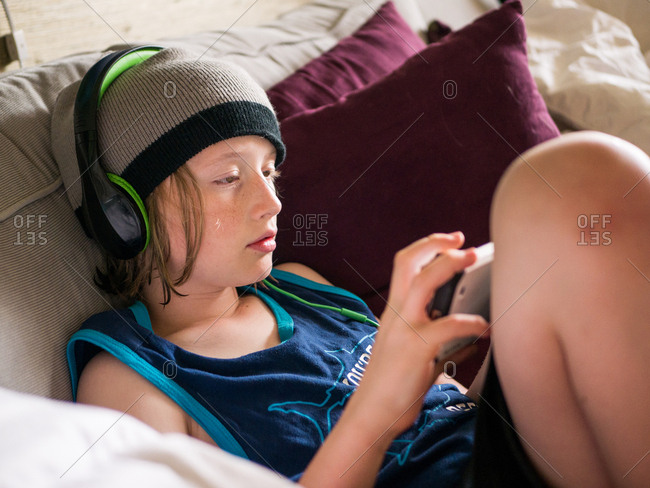 High angle view of boy using smart phone while listening music at home