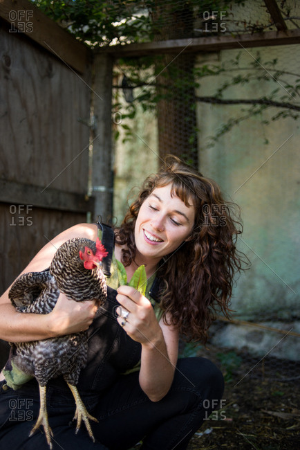 Happy woman feeding leaves to hen while crouching in poultry farm