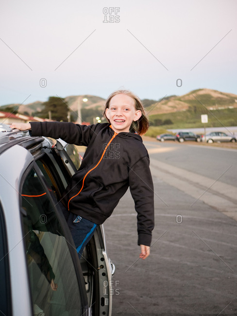 Happy boy looking away while standing in open car against clear sky