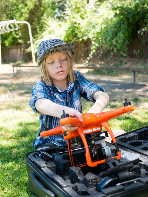Boy removing quadcopter from container while sitting in playground