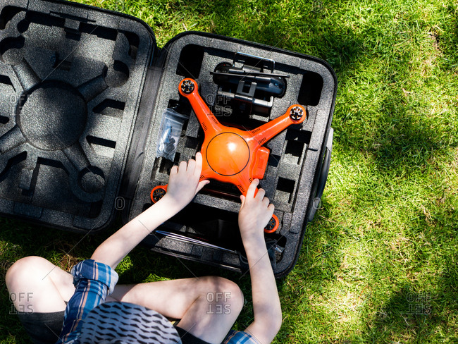 Overhead view of boy removing quadcopter from container while sitting on grassy field at playground