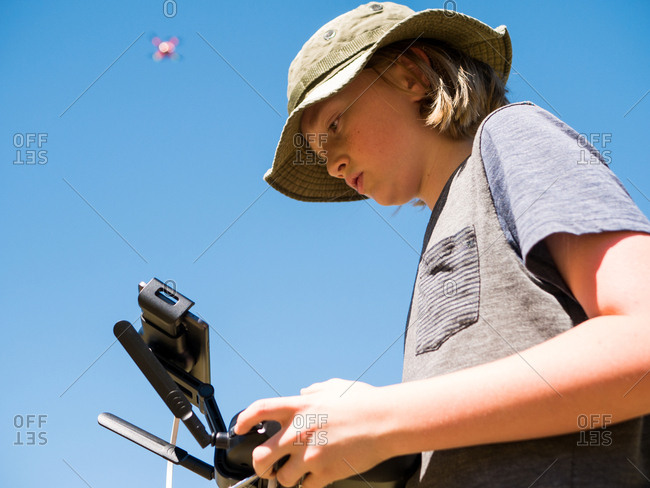 Low angle view of boy flying quadcopter using remote control against clear sky