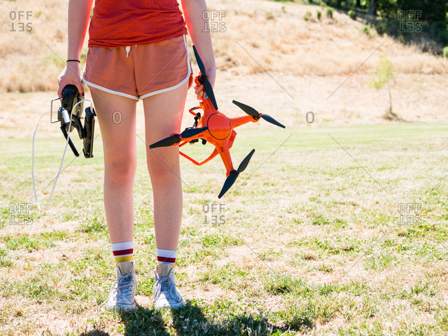 Low section of teenage girl holding remote control and quadcopter while standing at playground