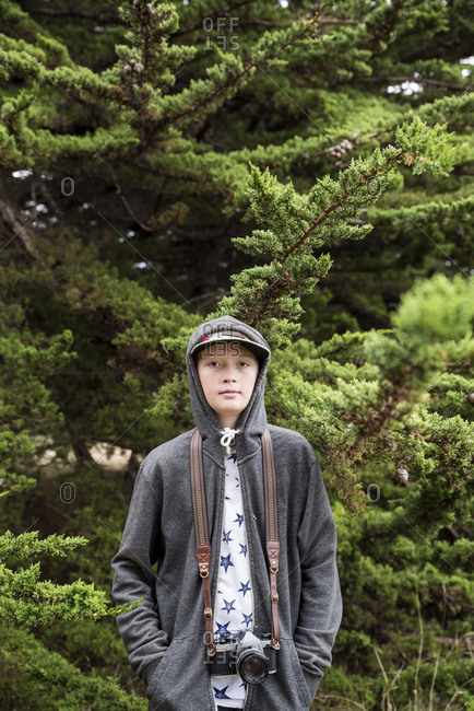 Portrait of confident boy with hands in pockets and camera wearing hooded jacket while standing against plants at park