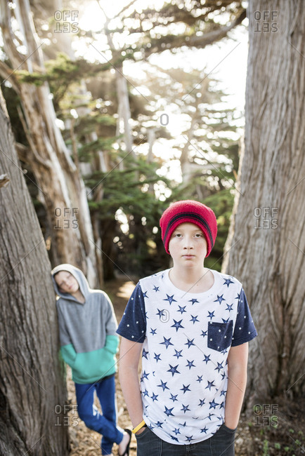 Portrait of confident boy with hands in pockets while friend standing by tree at park