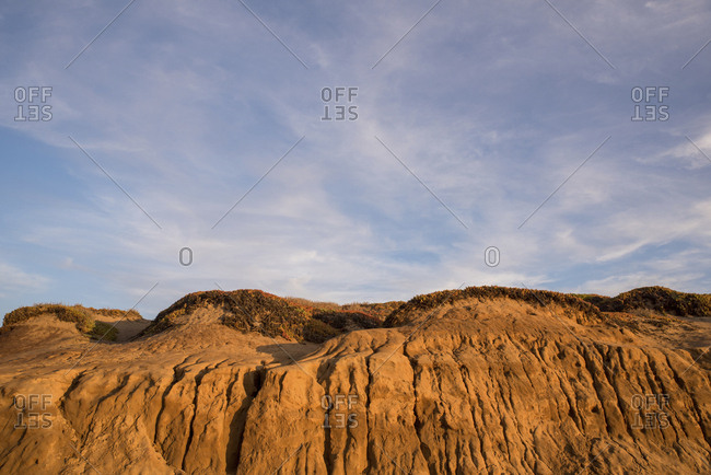 Low angle view of hill at beach against sky during sunset