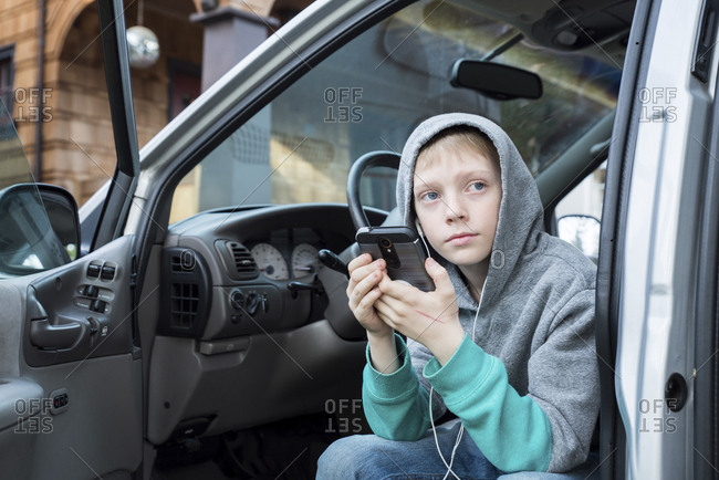 Boy wearing hooded shirt using mobile phone while sitting in car