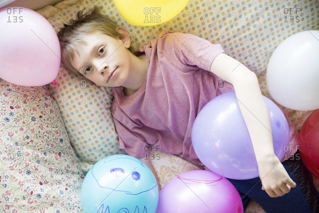 High angle portrait of boy with colorful balloons lying on bed at home