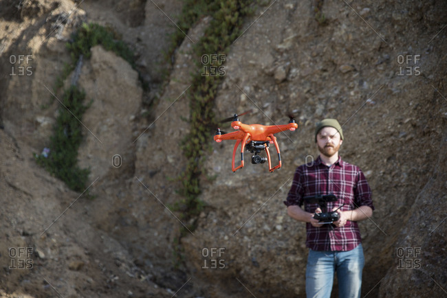 Man flying drone while standing against rock formation