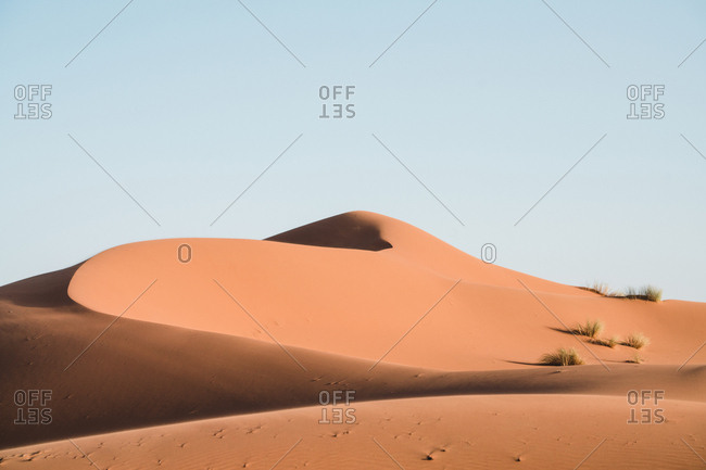 Idyllic view of sand dunes against clear sky