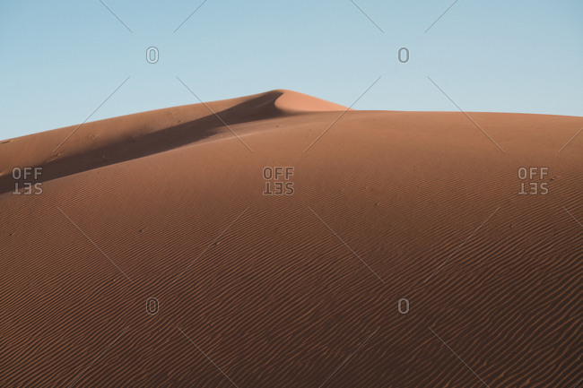 Tranquil view of sand dunes against clear sky