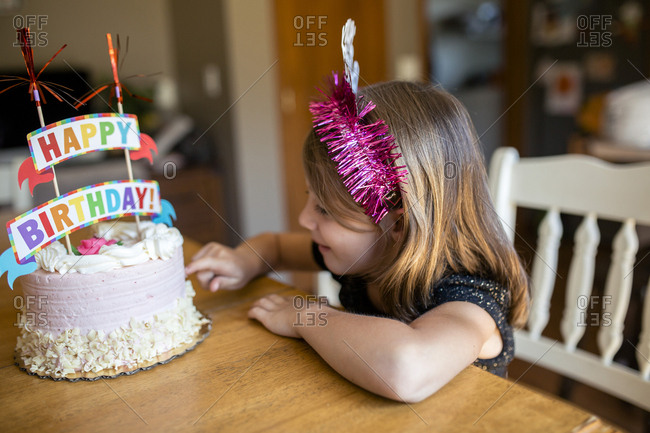 High angle view of girl touching birthday cake while sitting on chair at home