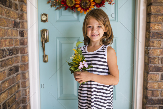 Portrait of happy girl holding leaves and flowers while standing against door on porch
