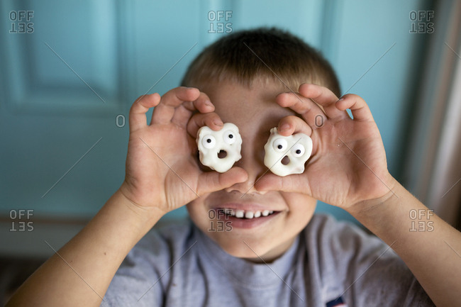 Close-up of happy boy holding anthropomorphic cookies against face