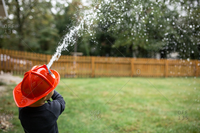 Rear view of boy wearing helmet while spraying water with garden hose at backyard