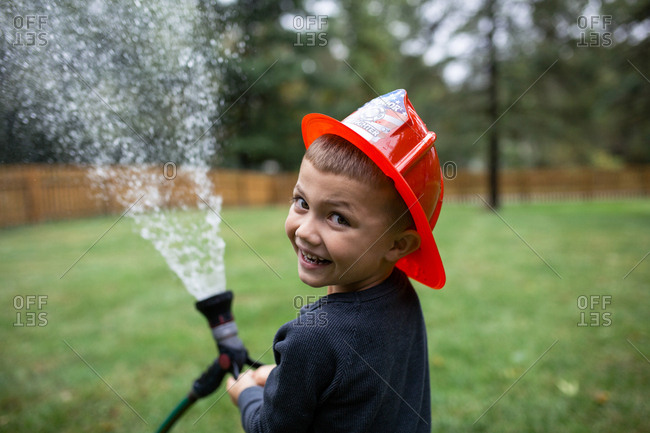 Portrait of boy wearing helmet while spraying water with garden hose at backyard
