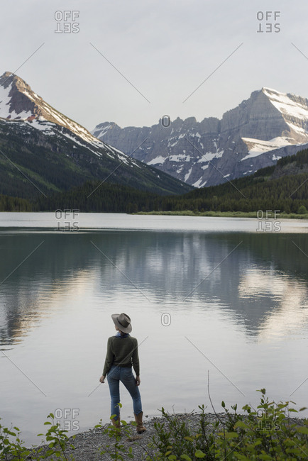 Rear view of female hiker looking at view while standing on shore by Swift current Lake