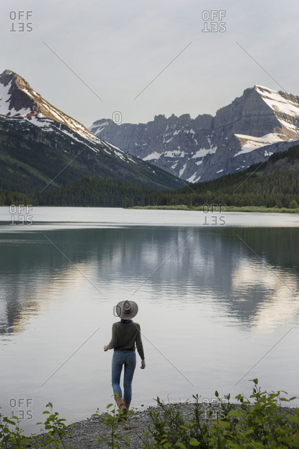 Rear view of female hiker looking at Mt. Grinnell while standing on shore by Swift current Lake