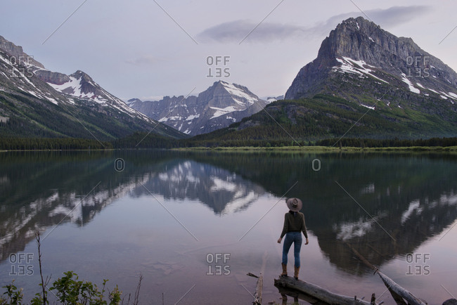 Rear view of female hiker looking at Mt. Grinnell while standing on wood by Swift current Lake