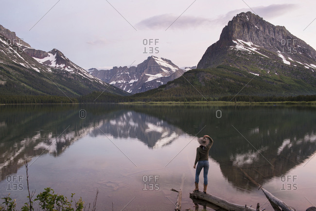 Rear view of hiker looking at Mt. Grinnell while standing on wood by Swift current Lake