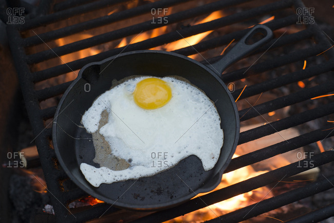 High angle view of egg in cast iron skillet on barbecue grill