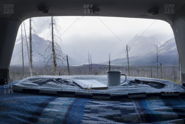 Mug and book on blanket at car trunk with Glacier National Park in background