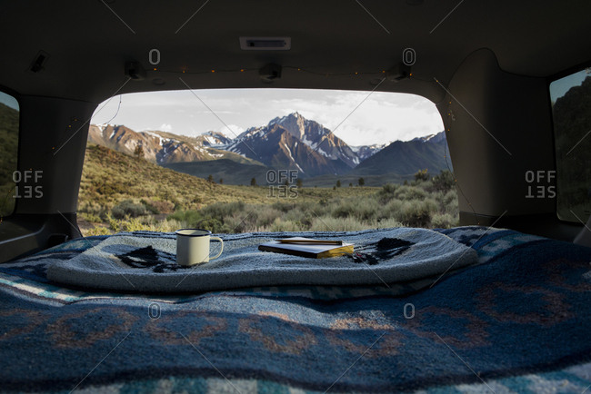 Book and mug on blanket at car trunk with Mount Morrison in background