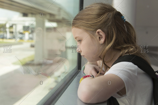 Side view of thoughtful girl looking through window