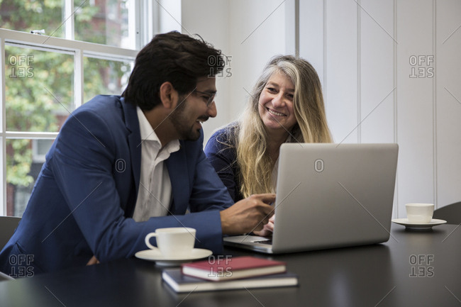 Smiling business people discussing over laptop computer at desk in office