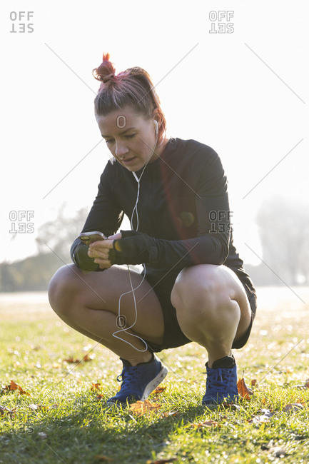 Full length of woman using smart phone while crouching on field at park during sunny day