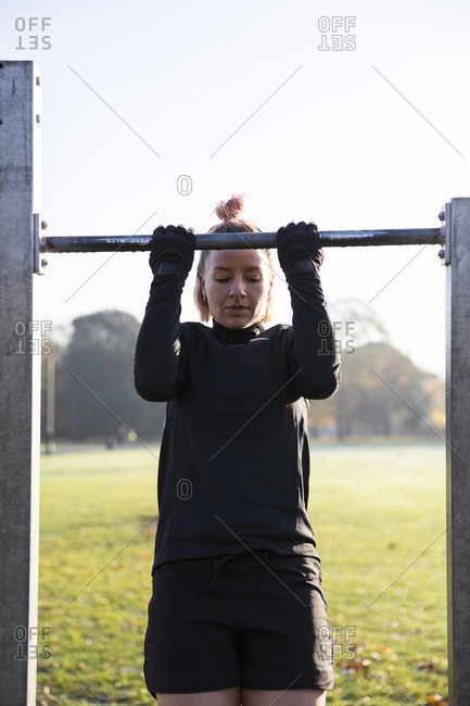 Woman doing chin-ups on exercise equipment at park