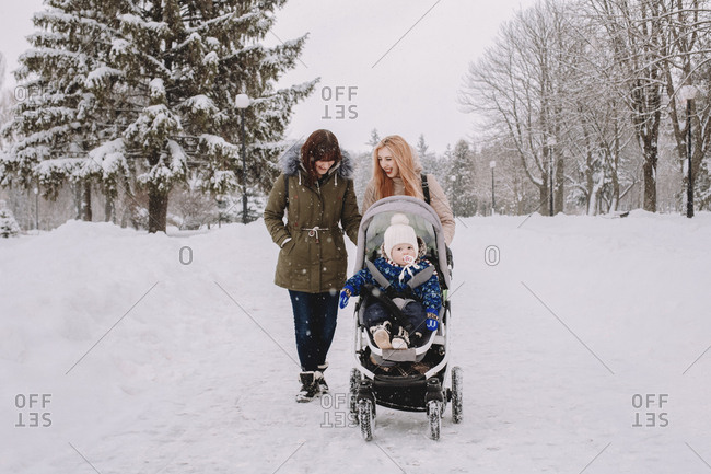 Lesbian mothers with cute son in baby stroller walking on snow covered field at park