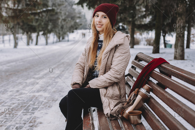 Portrait of smiling woman with insulated drink container sitting on bench against trees in park during winter