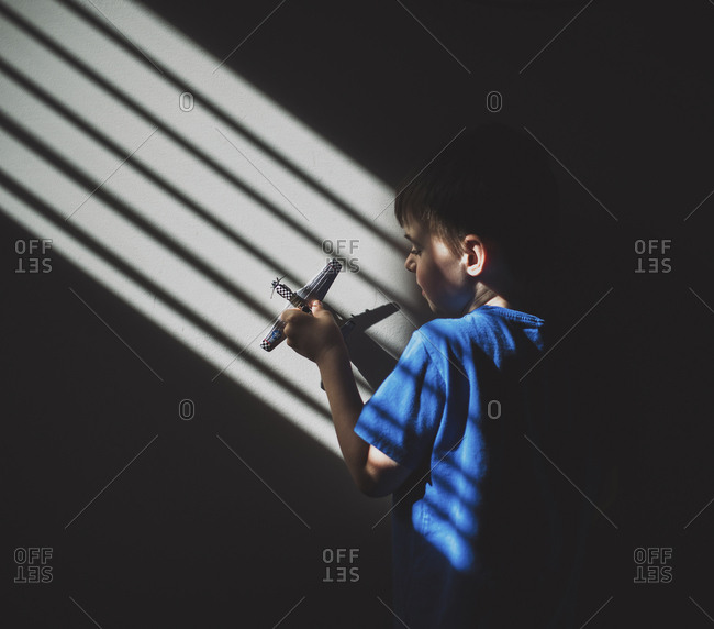 Sunlight falling on boy playing with toy airplane on wall in darkroom