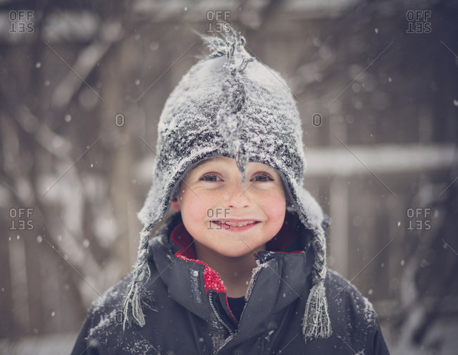 Portrait of cheerful boy wearing hat during snowfall