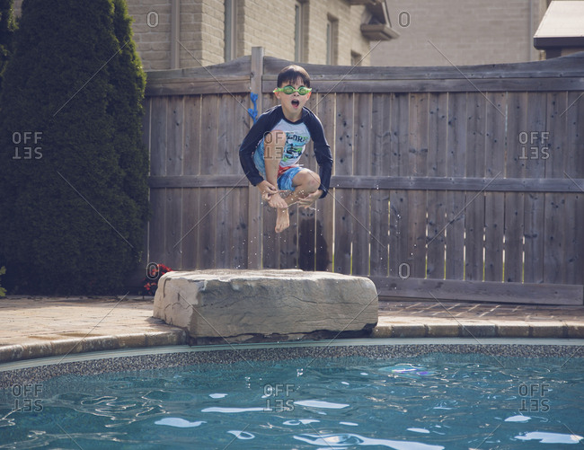 Carefree boy jumping into swimming pool against fence