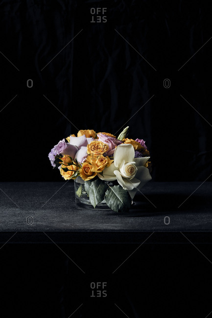 Colorful flowers in vase on table against black background