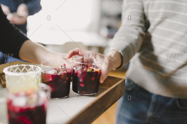 Cropped hand of woman serving drinks to male friend in party at home