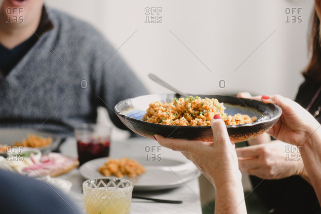 Cropped hands of woman holding rice while sitting with friends at dining table