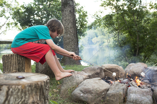 Side view of boy roasting marshmallow over campfire while sitting on tree stump at campsite
