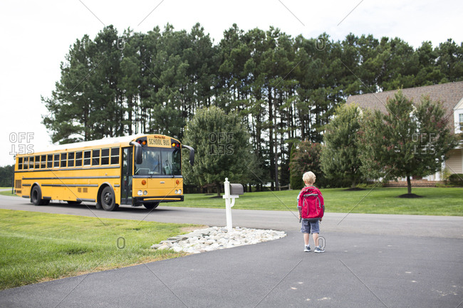 Rear view of boy with backpack waiting for school bus on road