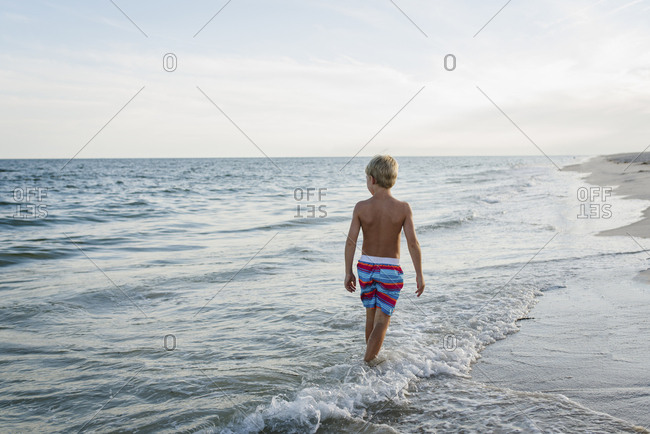 Rear view of shirtless boy walking at Tobay Beach in waves against sky
