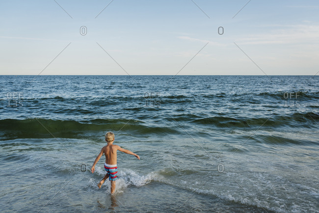 High angle view of shirtless boy playing in waves at Tobay Beach against sky
