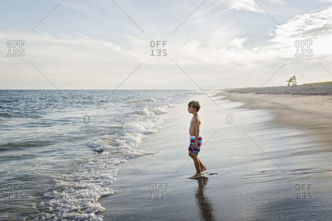 Side view of shirtless boy looking away while standing at Tobay Beach against sky