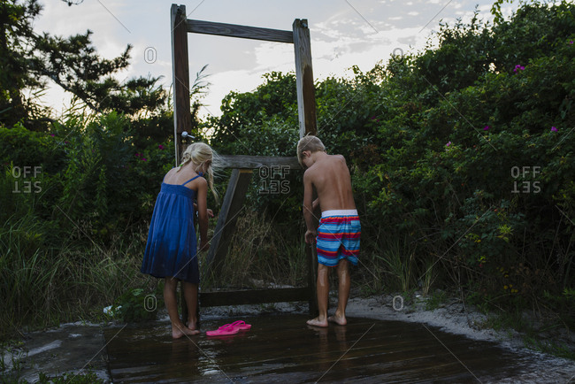Rear view of siblings washing legs from tap water at Tobay Beach
